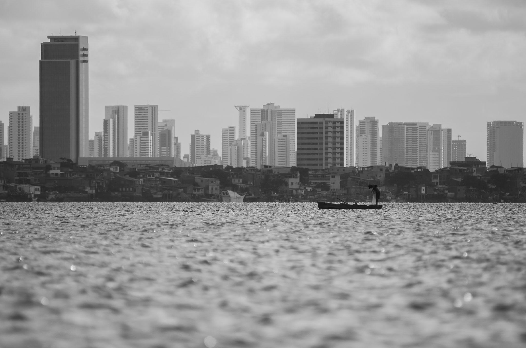 Passeio de barco no Rio Capibaribe (Recife). Na foto, pescador joga de rede de pescar no Rio Pina. Ao fundo, Brasília Teimosa e os prédios da zona sul do Recife (PE). Foto: Marcelo Soares.